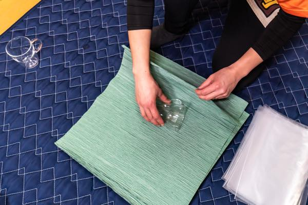 クレープ紙を下に敷き、グラスをくるみます。グラスの中にクレープ紙を入れ込むようにすると安全性が上がります。